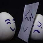ein lächelndes Ei und ein weinendes Ei, das sich hinter einen lächelden Smiley versteckt