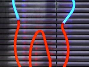 Neonlampe als Zahn in Blau und Rot