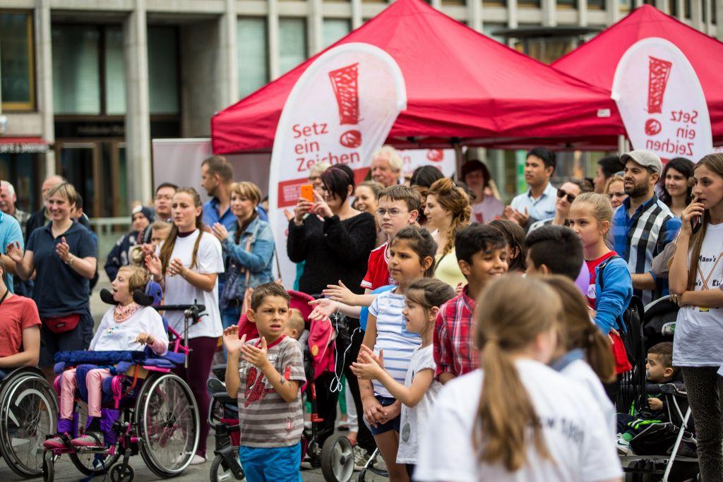 Menschen mit und ohne Rollstuhl beim Fackellauf in Berlin
