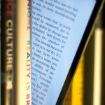 E-book-Reader steht zwischen Papierbüchern. Eine Ecke des Bildschirmes ragt hervor.