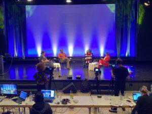 Die Talkrunde sitzt auf der Bühne mit Moderatorin Ninia Lagrande. Vor der Bühne stehen Kameras und ein Tisch mit Laptops, an denen Menschen arbeiten.