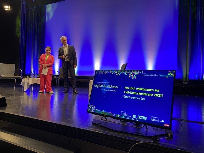 Moderatorin Ninia LaGrande und Prof. Dr. Thorsten Valk vom LVR-LandesMuseum auf der Bühne des Museums Beide schauen in die Kamera. Der Hintergrund wird blau angestrahlt Ninia LaGrande trägt einen pinken Anzug mit einem gelben Oberteil. Thorsten Falk trägt einen grauen Anzug und ein weißes Hemd. Im Vordergrund steht ein Bildschirm, wo steht: Herzlich Wilkommen zur LVR-Kulturkonfrenz. Gleich geht es los.
