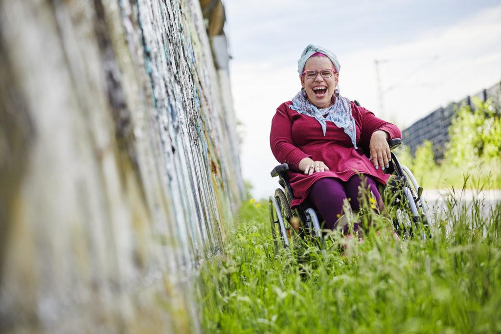 Tanja sitzt im Gras mit dem Rollstuhl. Neben ihr steht eine Wand mit Graffiti. Sie lacht sehr ausgiebig.